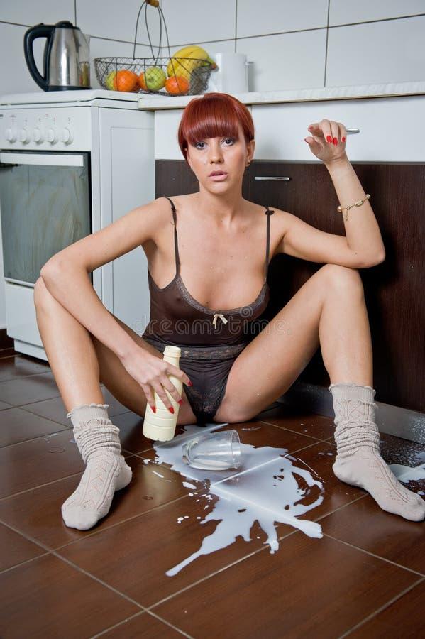 Download Mujer Atractiva Atractiva Que Se Sienta En El Piso De La Cocina Que Derrama La Leche De Una Botella Imagen de archivo - Imagen de caucásico, elegancia: 41910463