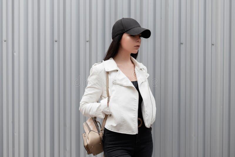 Mujer atractiva bonita en una gorra de béisbol negra de moda en una chaqueta de cuero blanca elegante en vaqueros imagen de archivo