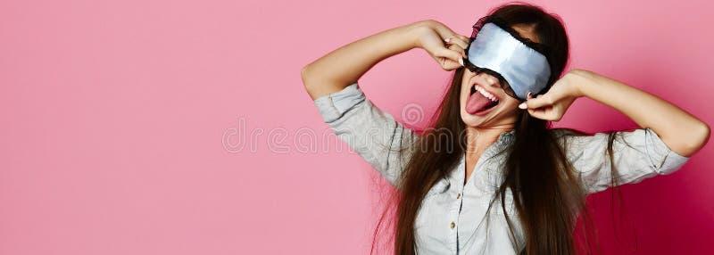 Mujer atractiva caucásica linda en la máscara del sueño que se divierte con el globo colorido sobre fondo rosado foto de archivo libre de regalías