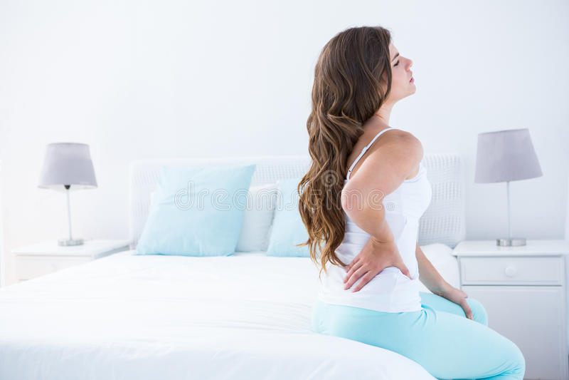 Mujer atractiva con dolor de espalda fotos de archivo
