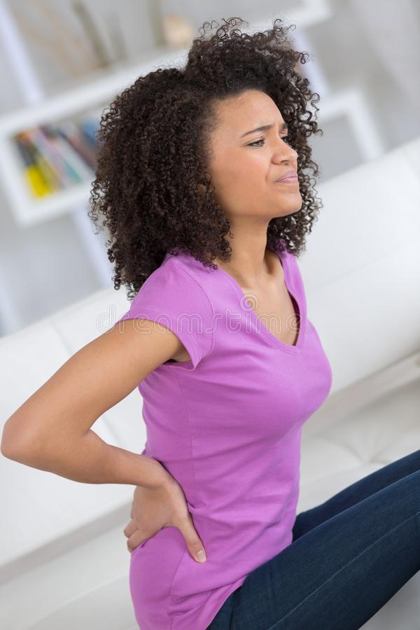 Mujer atractiva con dolor de espalda en casa en dormitorio fotografía de archivo