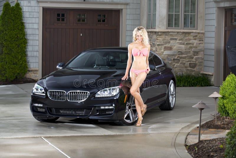 Mujer atractiva con el coche negro imagenes de archivo