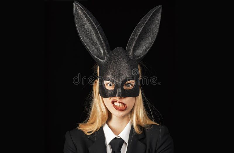 Mujer atractiva con el conejito de pascua de la m?scara en un fondo negro y miradas muy sensual Primer de gui?ar la cara de la mu foto de archivo libre de regalías
