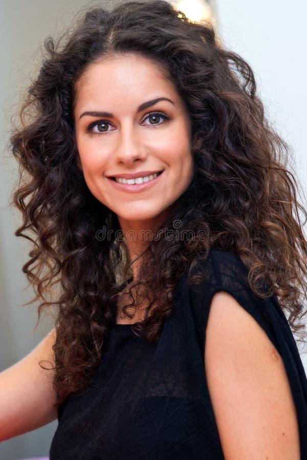 Mujer atractiva con el pelo rizado imagenes de archivo