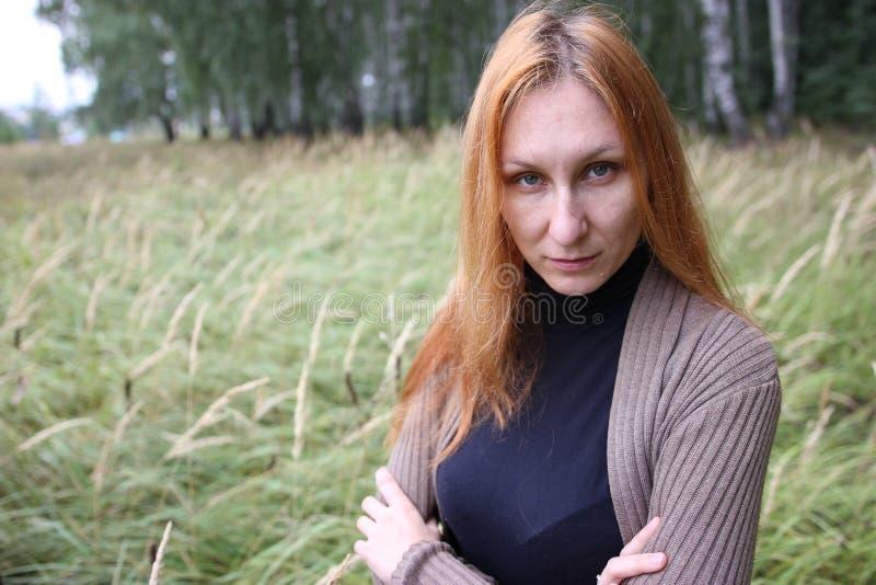 Mujer atractiva con el pelo rojo en el parque del otoño fotografía de archivo