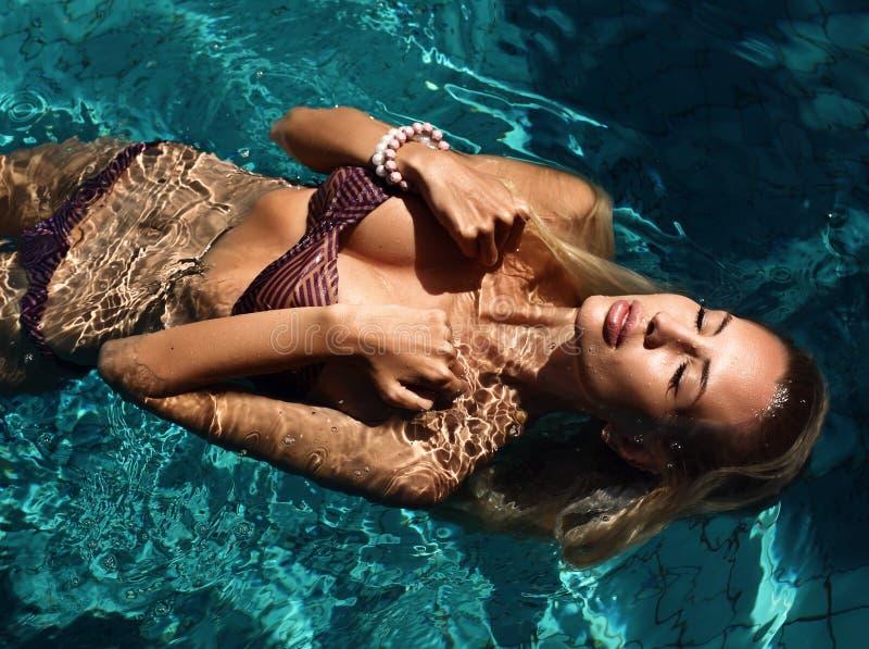 Mujer atractiva con el pelo rubio en el bikini que se relaja en piscina fotografía de archivo libre de regalías