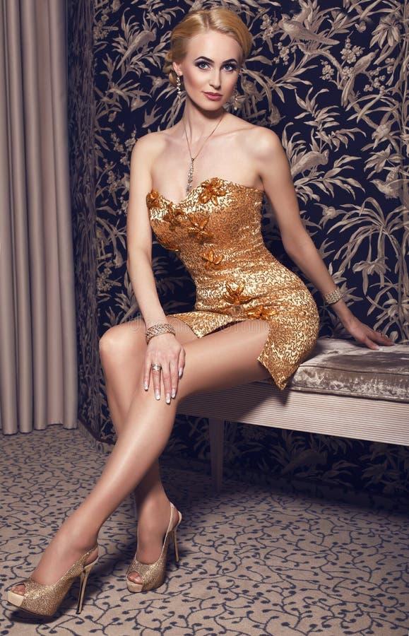 Mujer atractiva con el pelo rubio en vestido de lujo con joyería fotos de archivo