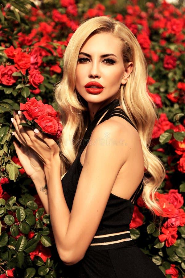Mujer atractiva con el pelo rubio en el vestido lujoso que presenta en la primavera g foto de archivo libre de regalías