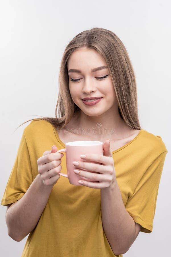 Mujer atractiva con el pelo rubio largo que sostiene la taza con té sabroso imagen de archivo libre de regalías
