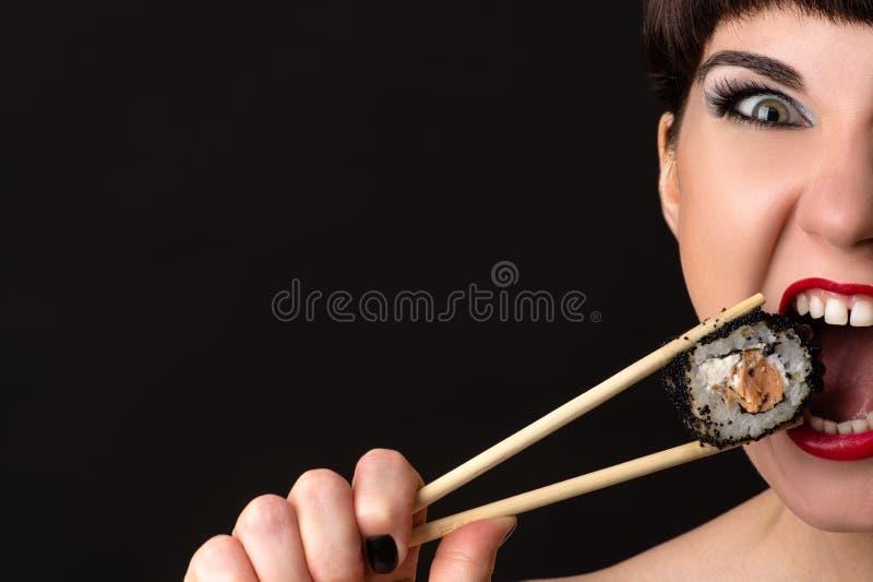 Mujer atractiva con la cara emocional que come el rollo imagen de archivo