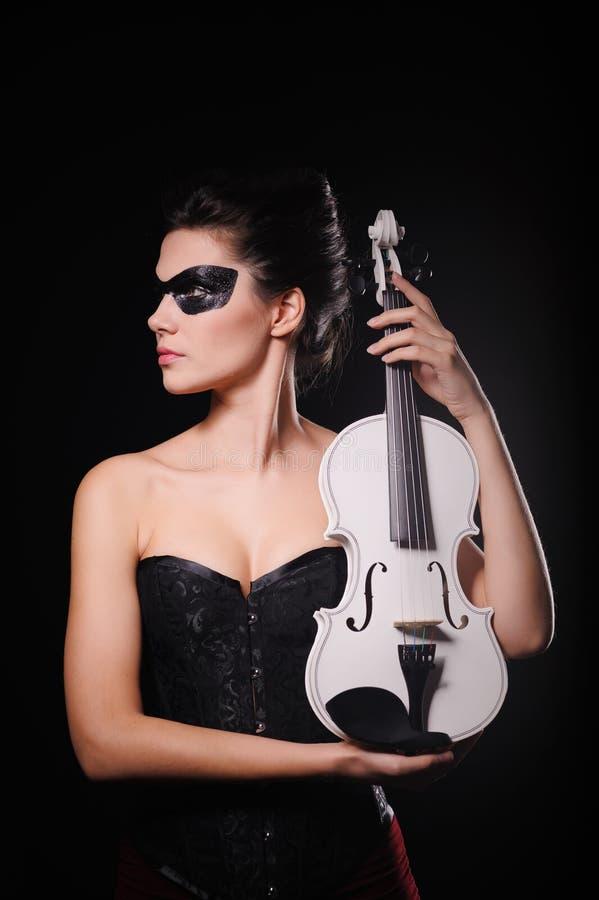 Mujer atractiva con la máscara negra del partido y el violín blanco fotografía de archivo