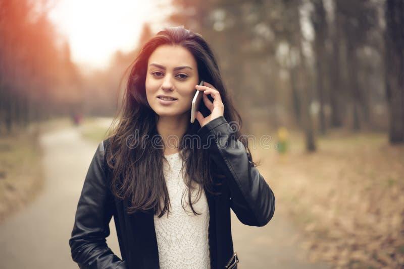 Mujer atractiva con las compras de la tarjeta de crédito en línea en el parque imagen de archivo