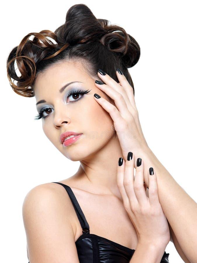 Mujer atractiva con los clavos creativos del peinado y del negro