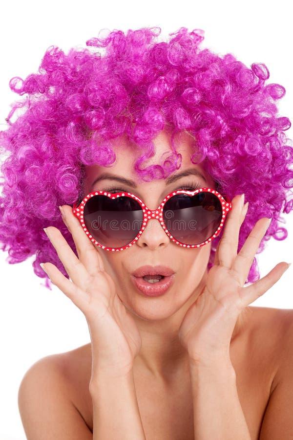 Mujer atractiva con los glasess de lujo y la peluca rosada imagen de archivo