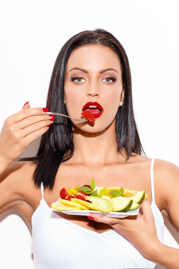 Mujer atractiva con los labios rojos que come la ensalada de fruta foto de archivo
