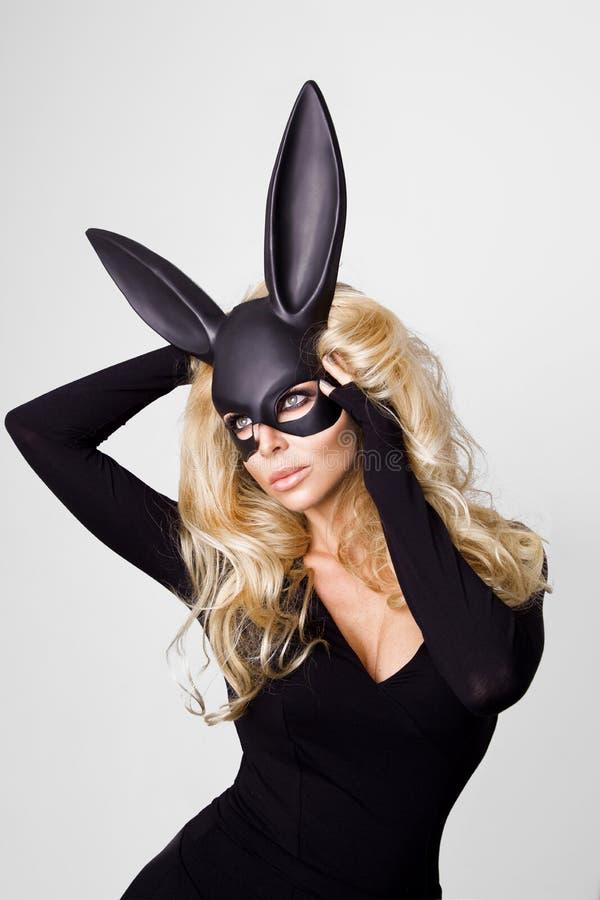 Mujer atractiva con los pechos grandes que llevan un conejito de pascua negro de la máscara que se coloca en un fondo blanco imagen de archivo