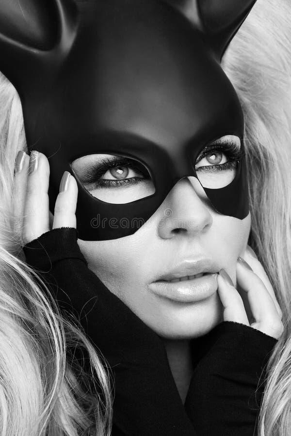 Mujer atractiva con los pechos grandes que llevan un conejito de pascua negro de la máscara que se coloca en un fondo blanco foto de archivo libre de regalías