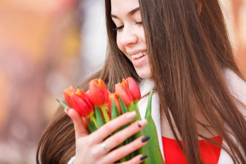 Mujer atractiva con los tulipanes foto de archivo