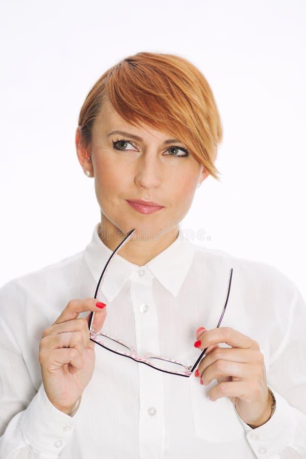 Mujer atractiva con los vidrios que echan un vistazo de lado imagen de archivo libre de regalías