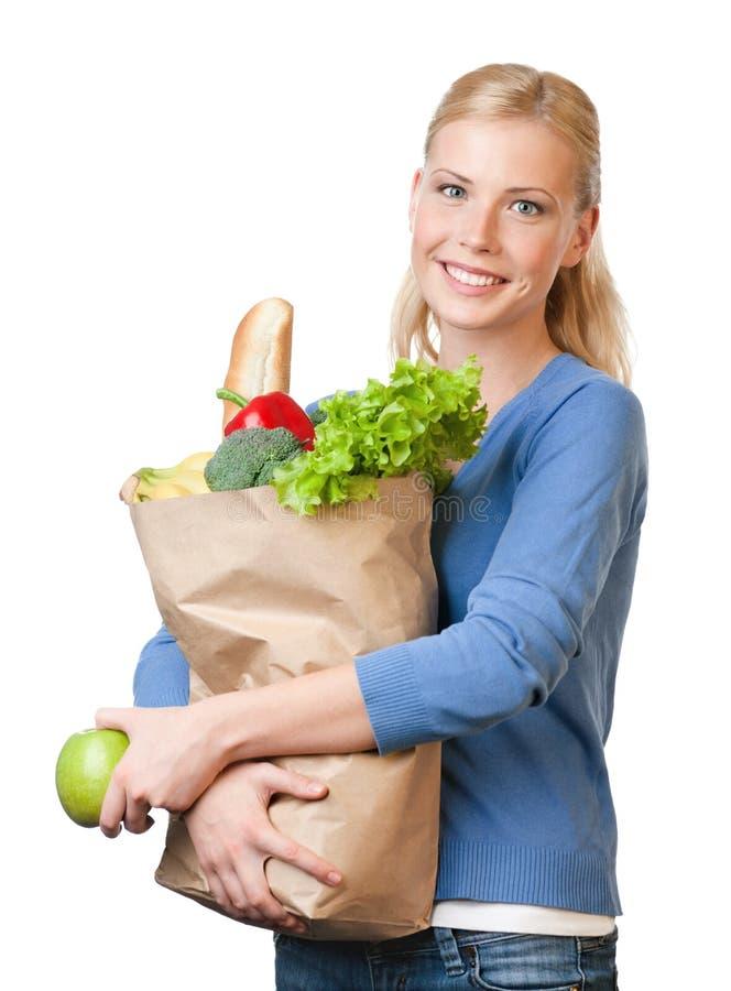 Mujer atractiva con un bolso lleno de consumición sana imagen de archivo