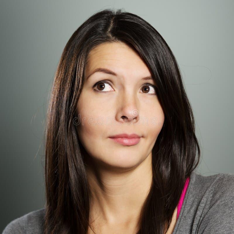 Mujer atractiva con una expresión escéptica fotos de archivo