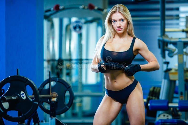 Mujer atractiva de la aptitud brutal con un muscular en el gimnasio Deportes y aptitud - concepto de forma de vida sana Mujer de  foto de archivo libre de regalías