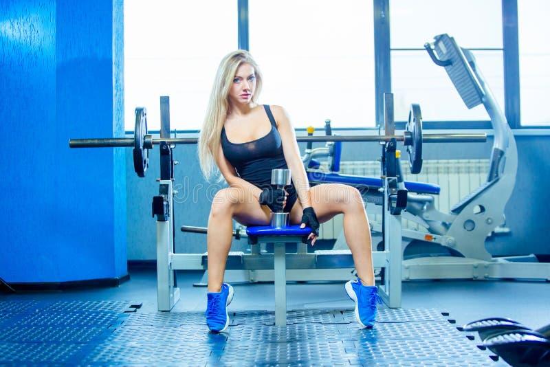 Mujer atractiva de la aptitud brutal con un muscular en el gimnasio Deportes y aptitud - concepto de forma de vida sana Mujer de  imagenes de archivo