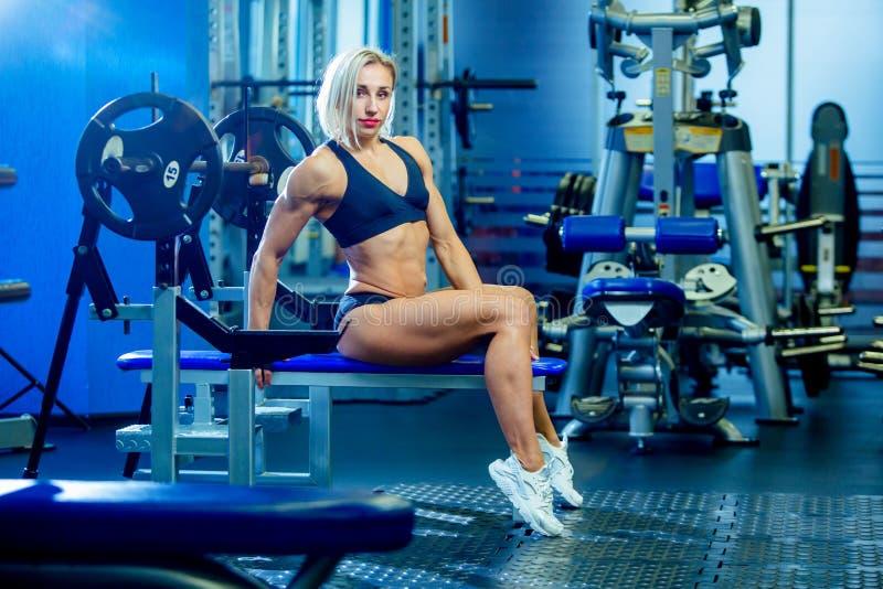 Mujer atractiva de la aptitud brutal con un muscular en el gimnasio Deportes y aptitud - concepto de forma de vida sana Mujer de  fotografía de archivo libre de regalías