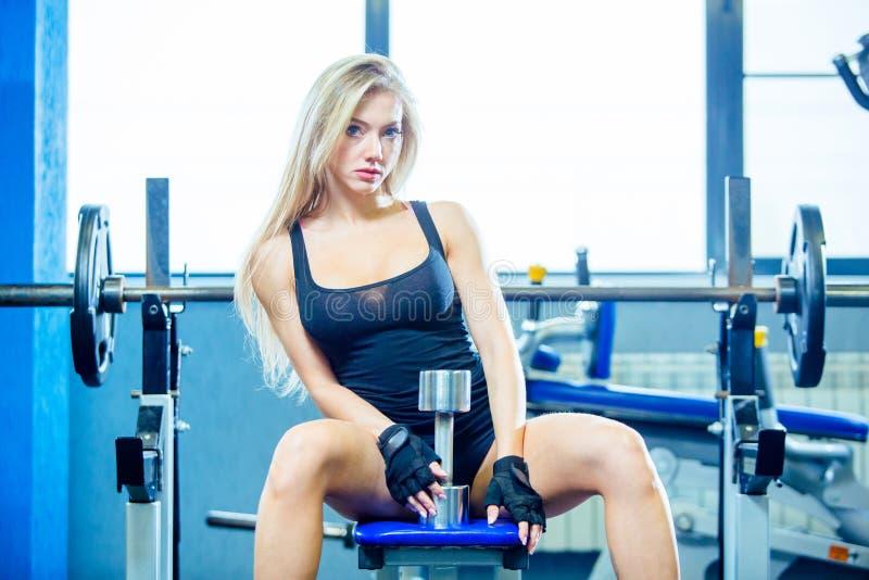 Mujer atractiva de la aptitud brutal con un muscular en el gimnasio Deportes y aptitud - concepto de forma de vida sana Mujer de  fotos de archivo libres de regalías