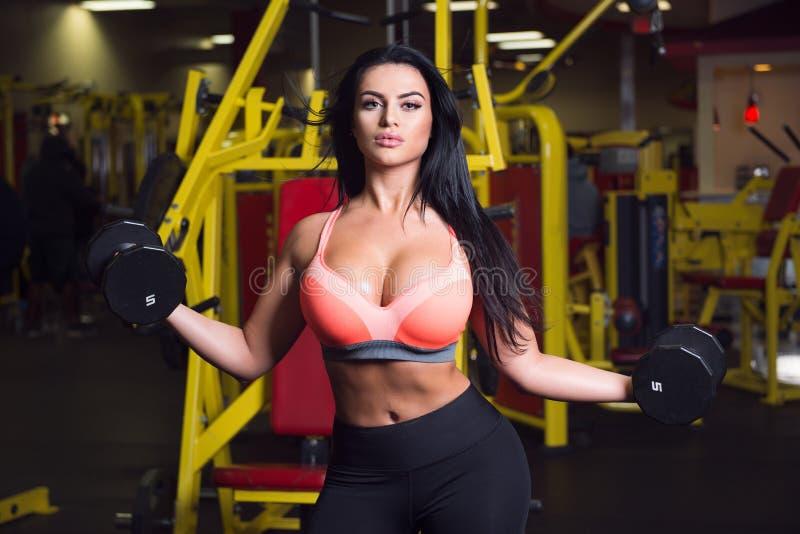 Mujer atractiva de la aptitud que hace entrenamiento del deporte en el gimnasio con pesas de gimnasia foto de archivo libre de regalías