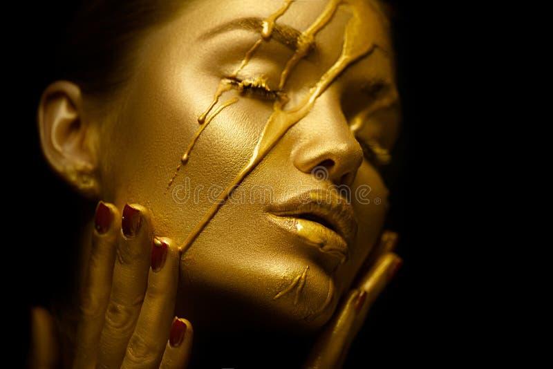 Mujer atractiva de la belleza con la piel metálica de oro La pintura del oro mancha goteos de la cara y de los labios atractivos fotografía de archivo libre de regalías
