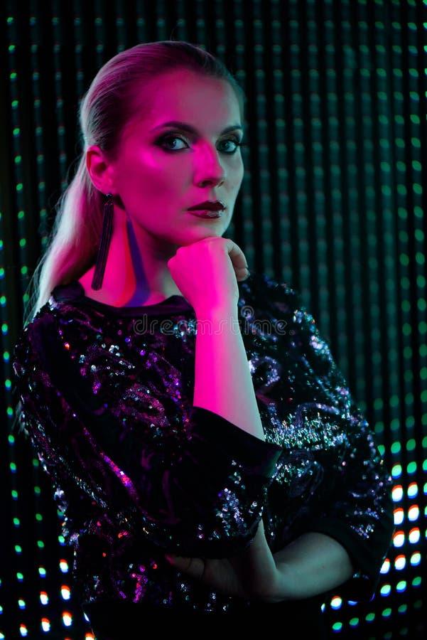 Mujer atractiva de la belleza que presenta sobre fondo de neón rojo de la ciudad de la noche y azul dramático fotos de archivo libres de regalías