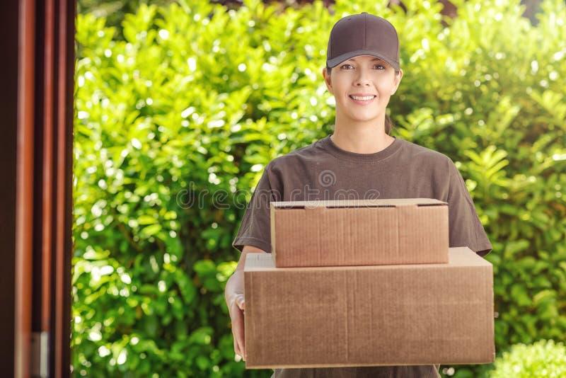 Mujer atractiva de la entrega con dos cajas de cartón fotografía de archivo