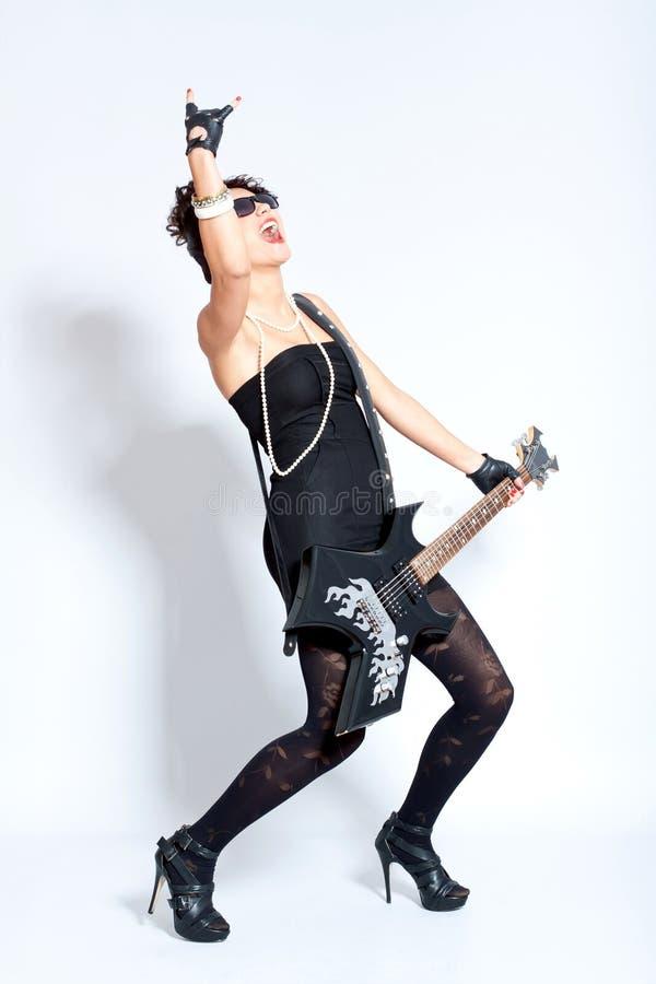 Mujer atractiva de la manera que toca una guitarra eléctrica imagen de archivo