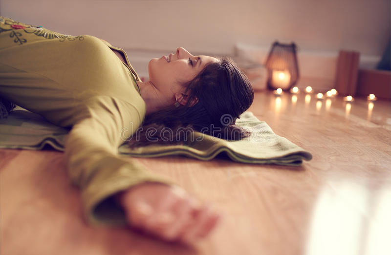 Mujer atractiva de la raza mixta que hace yoga restaurativa foto de archivo libre de regalías