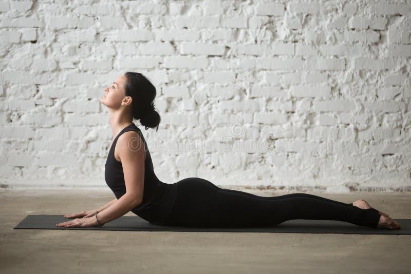 Mujer atractiva de la yogui joven en la actitud de la cobra, fondo blanco del desván fotos de archivo libres de regalías