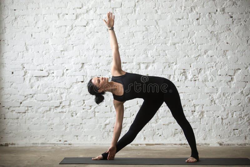 Mujer atractiva de la yogui joven en la actitud de Utthita Trikonasana, l blanco foto de archivo