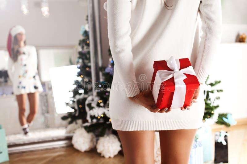 Mujer atractiva de Papá Noel con un regalo de Navidad en su mano fotos de archivo