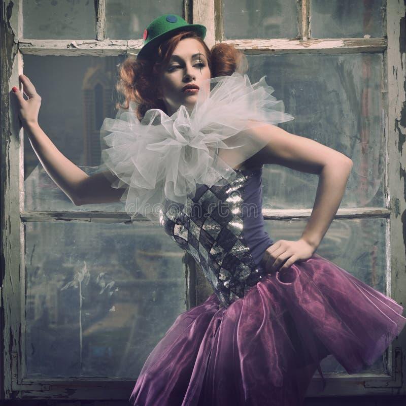 Mujer atractiva de Pierrot detrás de la ventana fotos de archivo