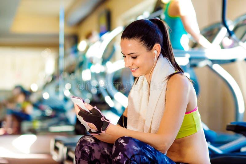 Mujer atractiva del ajuste en un gimnasio con el teléfono elegante imagen de archivo libre de regalías