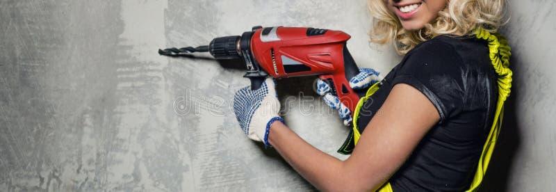 Mujer atractiva del constructor con una imagen horizontal del taladro foto de archivo