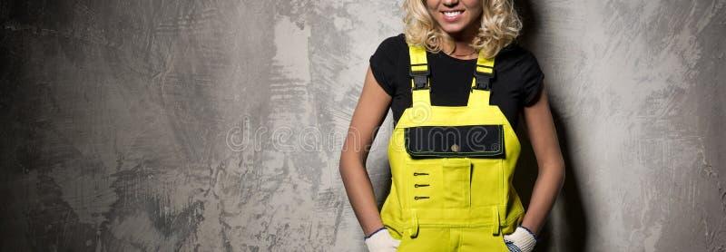 Mujer atractiva del constructor de la imagen horizontal en la pared del grunge foto de archivo libre de regalías
