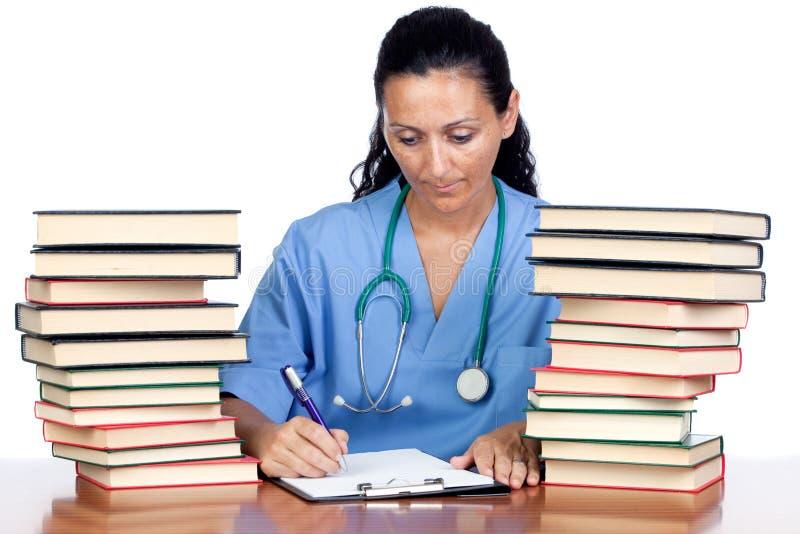 Mujer atractiva del doctor con la escritura de muchos libros imagen de archivo libre de regalías