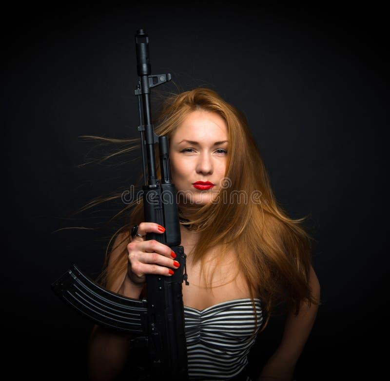 Mujer atractiva del encanto de la moda que soporta su rifle de asalto del arma g imagenes de archivo