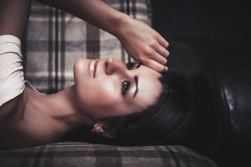 Mujer atractiva del encanto moreno hermoso que presenta en el sofá imagenes de archivo
