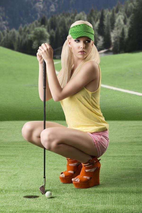 Mujer atractiva del jugador de golf plegada fotos de archivo