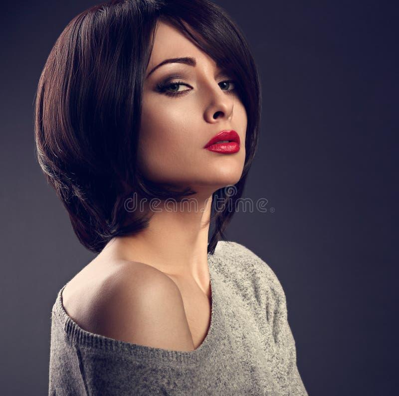 Mujer atractiva del maquillaje hermoso con estilo de pelo corto con el rojo caliente l imagen de archivo
