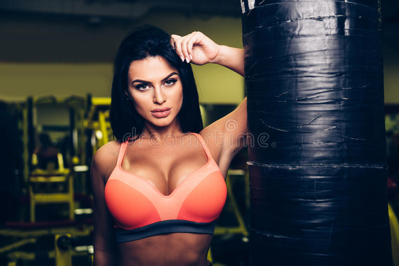 Mujer atractiva del modelo de la aptitud que presenta cerca del saco de arena en gimnasio del deporte imágenes de archivo libres de regalías