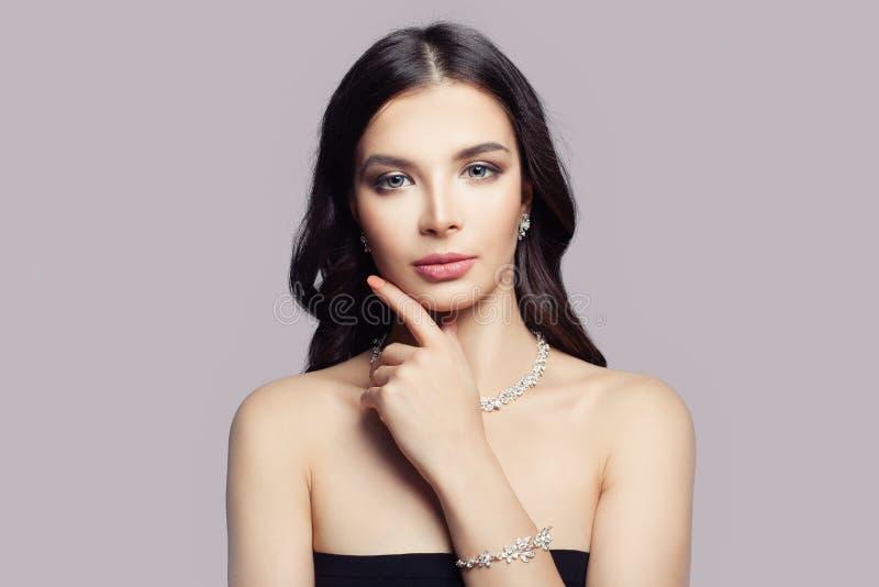 Mujer atractiva del modelo de moda con maquillaje y collar de diamantes y pulsera en fondo rosado foto de archivo