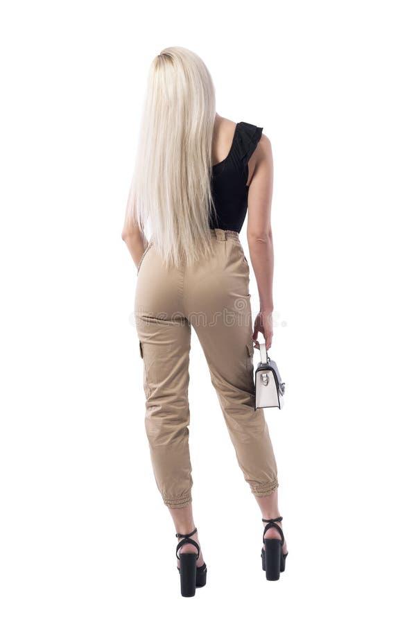 Mujer atractiva del pelo rubio en pantalones del color crema con esperar del bolso Visi?n posterior fotos de archivo